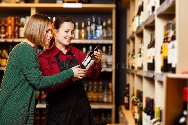Foto aan kant van twee gelukkige vrouwen met fles wijn in opslag op achtergrond van planken royalty-vrije stock afbeelding