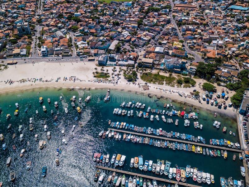 Foto aerea del fuco dei pescherecci nell'acqua blu Città brasiliana Arraial fare Cabo ed il DOS Anjos della Praia della spiaggia fotografie stock