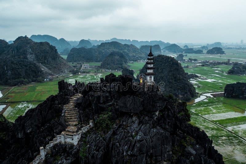 Foto aerea del fuco - donna accanto ad un santuario in cima ad una montagna nel Vietnam del Nord Hang Mua fotografia stock