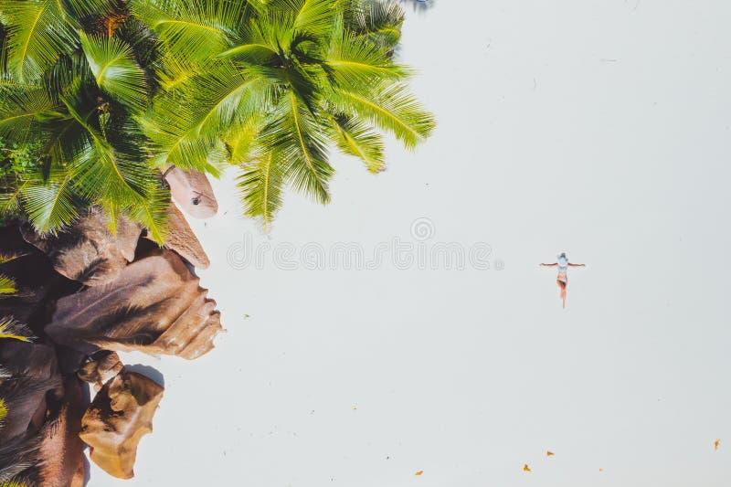 Foto aerea della giovane donna che mette su spiaggia tropicale esotica con la sabbia bianca Ragazza che prende il sole e che si r fotografia stock libera da diritti