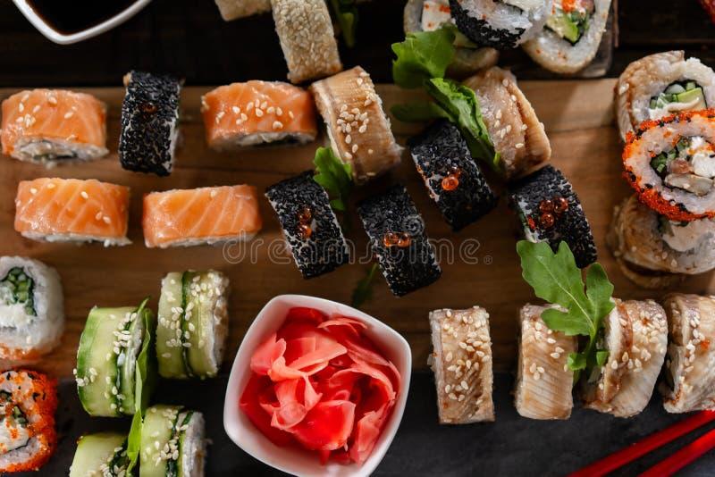 Foto ajustada do alimento do sushi Rolls serviu na placa marrom de madeira e da ardósia Feche acima da vista do gengibre conserva foto de stock