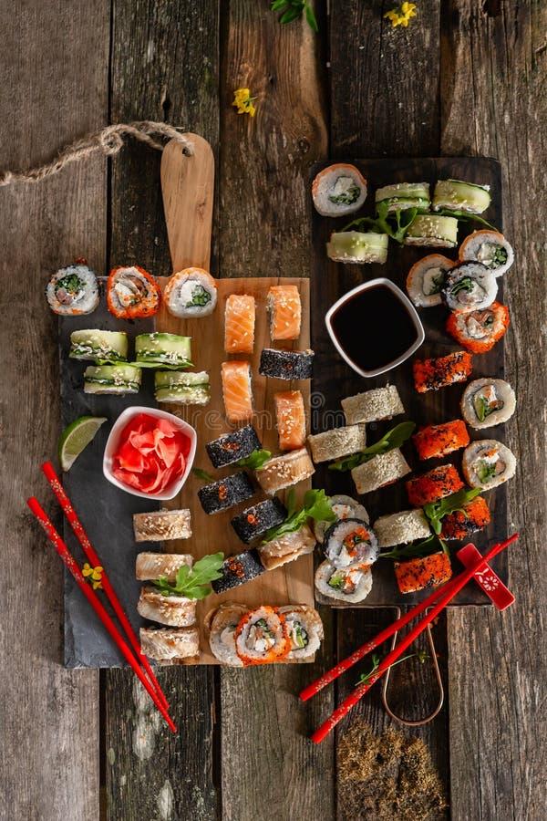 Foto ajustada do alimento do sushi Rolls serviu na placa marrom de madeira e da ardósia Opinião ascendente e superior do fim do s fotos de stock