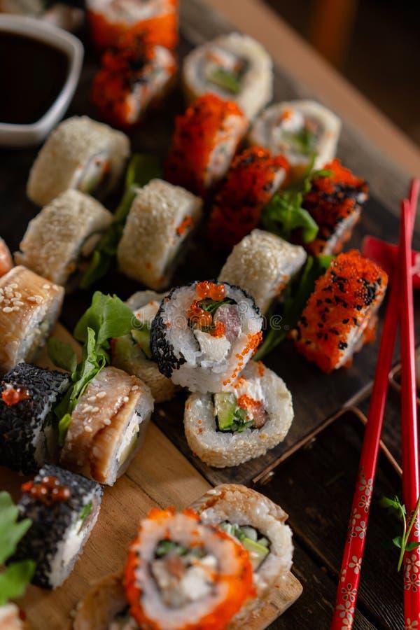 Foto ajustada do alimento do sushi Rolls serviu na placa marrom de madeira e da ardósia Opinião ascendente e superior do fim do s imagens de stock
