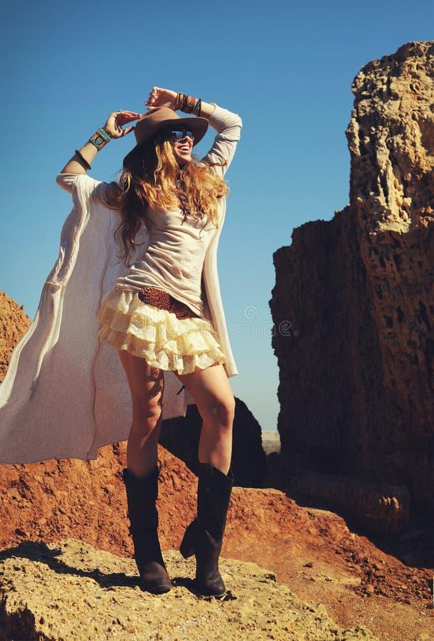 Foto al aire libre de la moda de la mujer feliz joven en sombrero, incorporándose en una piel contra rocas, manos fotografía de archivo