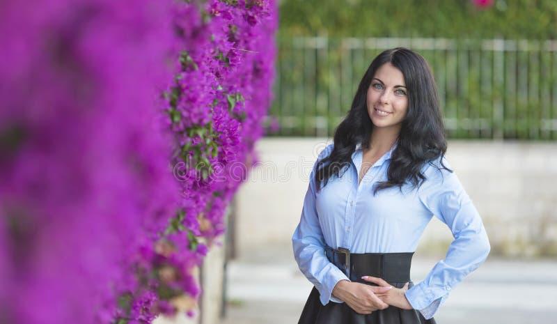 Foto all'aperto di modo di bella giovane donna circondata dai fiori fotografia stock libera da diritti