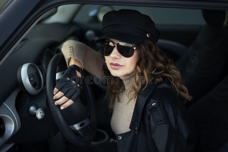 Foto all'aperto di modo della donna con capelli scuri in bomber nero ed occhiali da sole che posano in retro automobile fotografia stock