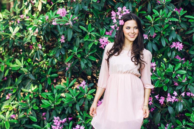 Foto all'aperto di modo di bella giovane donna circondata dai fiori Fiore della sorgente fotografia stock libera da diritti