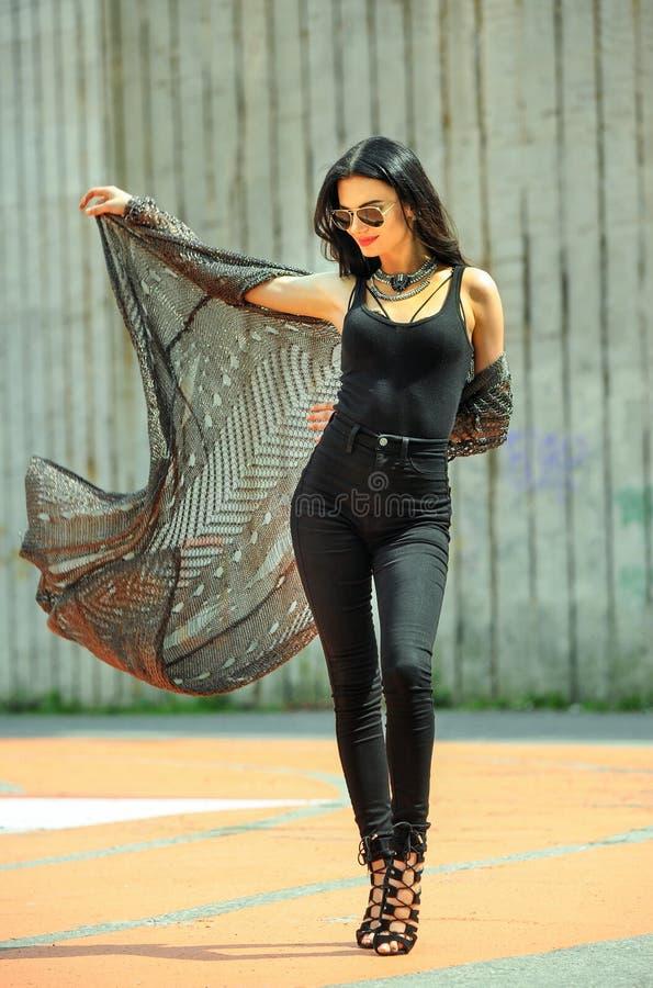 Foto all'aperto di stile della via di modo della giovane donna graziosa in attrezzatura d'avanguardia che cammina nella città immagine stock libera da diritti