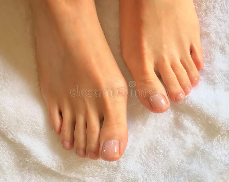 Foto alta vicina dei piedi e delle dita del piede della donna su un asciugamano bianco fotografia stock