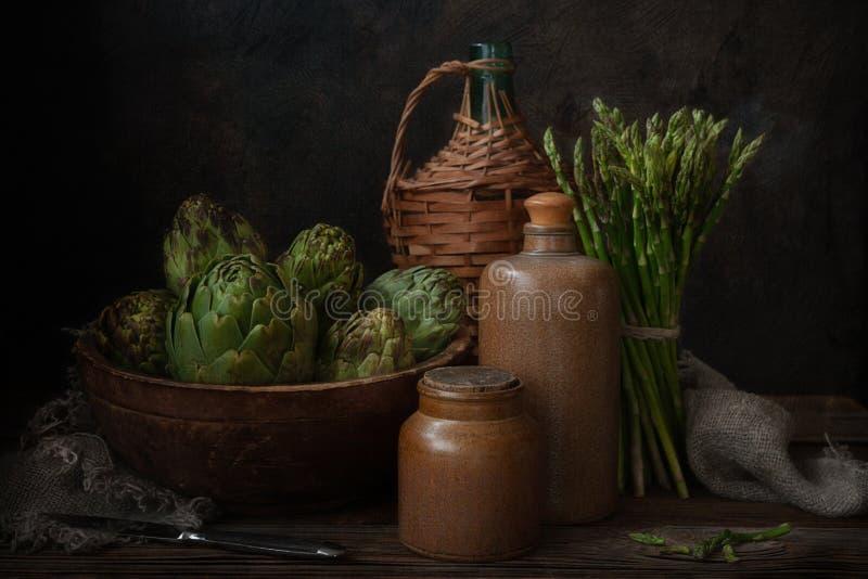 Foto alta vicina del carciofo fresco nella vecchi ciotola e mazzo di legno di asparago verde Natura morta su fondo scuro immagine stock libera da diritti