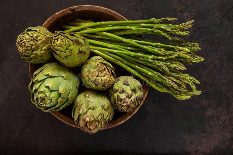 Foto alta vicina del carciofo fresco nella vecchi ciotola e mazzo di legno di asparago verde Vista superiore su fondo scuro fotografia stock