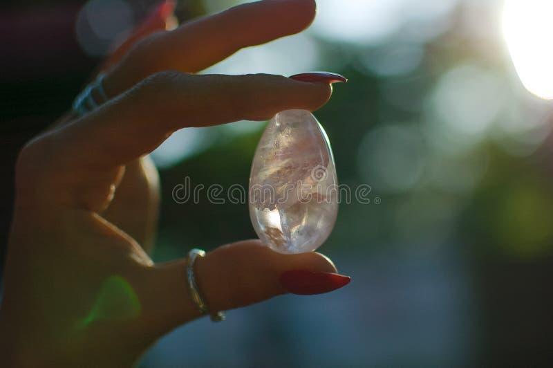 Foto alta vicina della mano femminile con l'uovo ametista trasparente di yoni per vumbuilding Uovo del cristallo di quarzo in man immagine stock