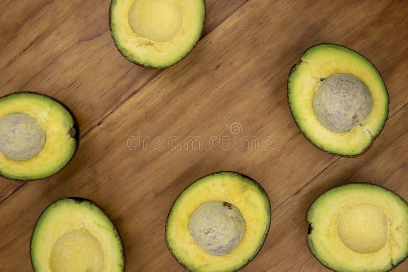 Foto amarela verde da opinião superior do abacate Corte o vegetal do abacate na placa de madeira Fruto exótico com gosto delicios foto de stock royalty free