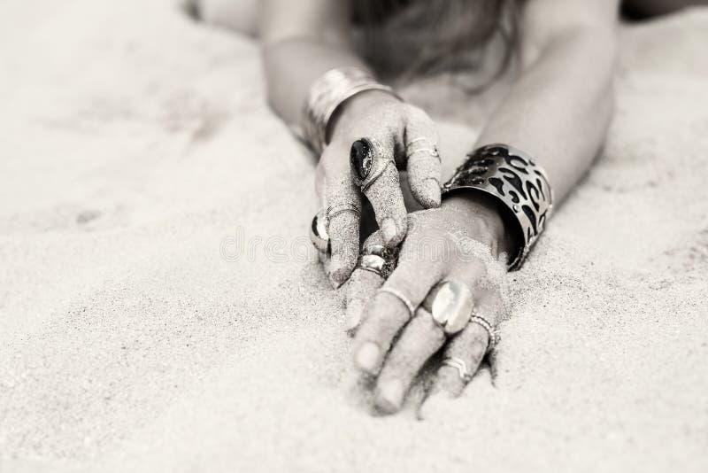 Foto artistica delle mani femminili con gioielli coperti di grani di sabbia fotografia stock libera da diritti
