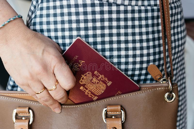 Foto ascendente cercana de la mujer elegante que saca a pasaporte español el monedero imagenes de archivo