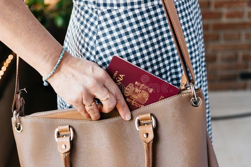 Foto ascendente cercana de la mujer elegante que saca a pasaporte español el monedero fotografía de archivo