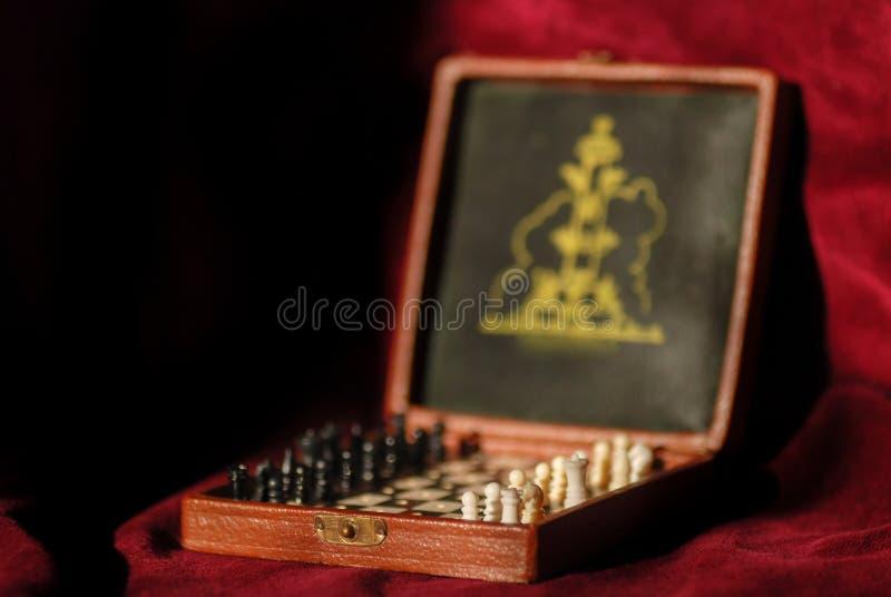 Foto ascendente cercana del mini tablero de ajedrez del bolsillo en fondo rojo imagen de archivo libre de regalías
