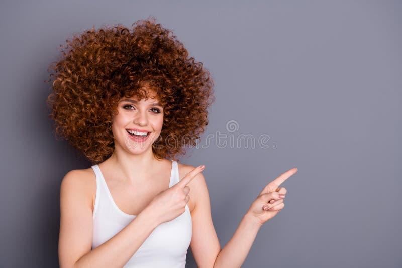 A foto ascendente próxima da senhora bonita na moda manda o conselho das propagandas recomendar pontas isolada sobre o fundo cinz fotos de stock royalty free