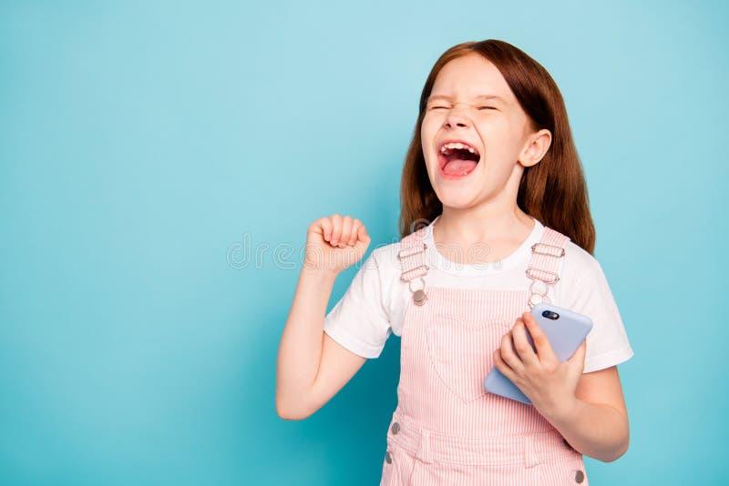 A foto ascendente próxima das mãos deleitadas do aumento da criança grita os olhos yeah próximos tem macacões na moda à moda do d fotografia de stock