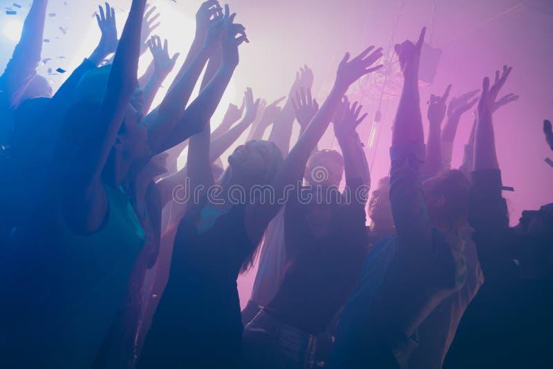 A foto ascendente próxima de muitas mãos roxas de dança do clube noturno da névoa dos confetes das luzes do clubbing dos povos da imagens de stock royalty free