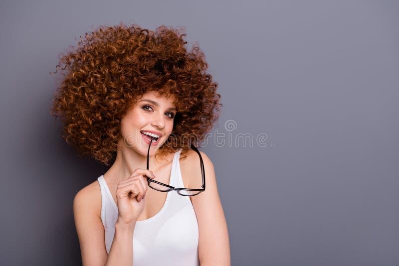A foto ascendente próxima do olhar foxy bonito da senhora quis saber pensa sobre a camiseta de alças branca das especs. do desgas fotografia de stock
