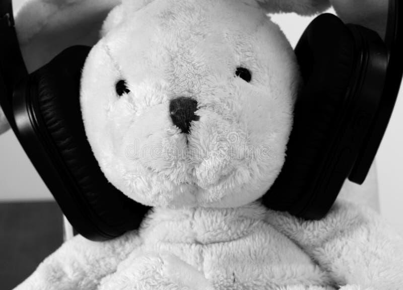 Foto ascendente próxima em preto e branco de um brinquedo do luxuoso do coelho com fones de ouvido sem fio foto de stock royalty free