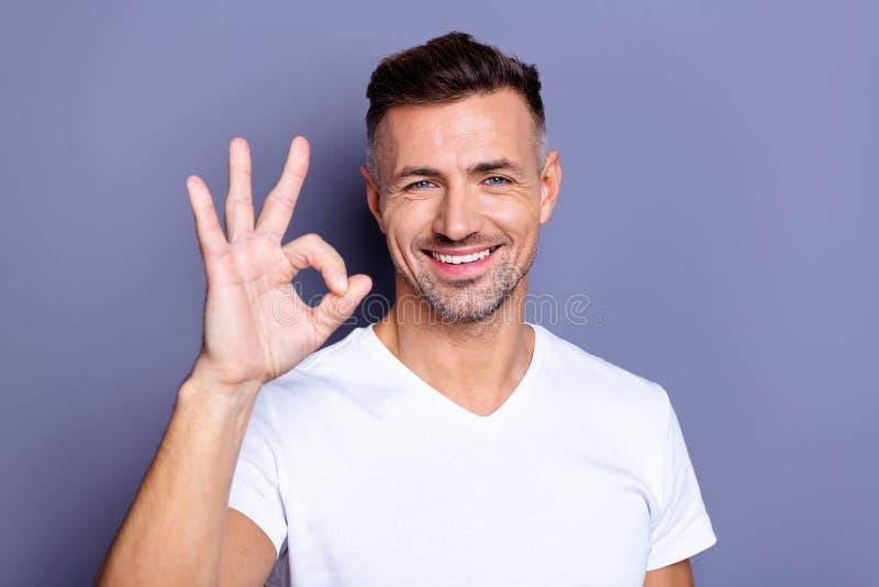 Foto ascendente próxima que surpreende ele seu braço de mão perfeito macho da aparência da Idade Média levantou o símbolo do okey foto de stock royalty free