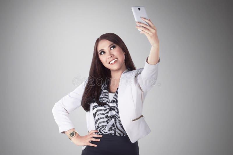 Foto asiática del selfie de la toma de la mujer de negocios con su teléfono móvil foto de archivo libre de regalías