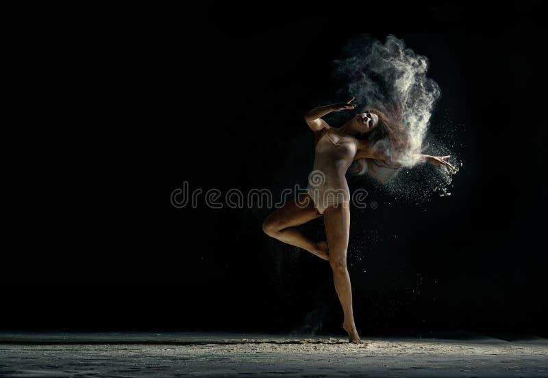 Foto asombrosa del baile agraciado de la mujer con polvo fotos de archivo
