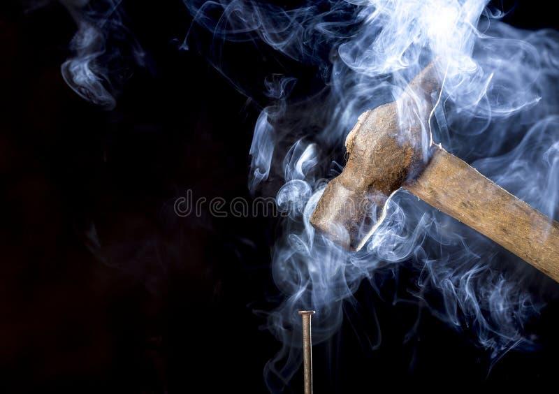 Foto astratta del martello arrugginito del metallo sopra il chiodo con fumo su fondo nero immagini stock
