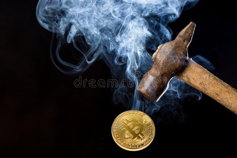 Foto astratta del martello arrugginito del metallo sopra bitcoin con fumo su fondo nero fotografie stock