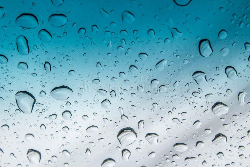 Foto astratta di goccia di acqua sullo specchio blu fotografia stock