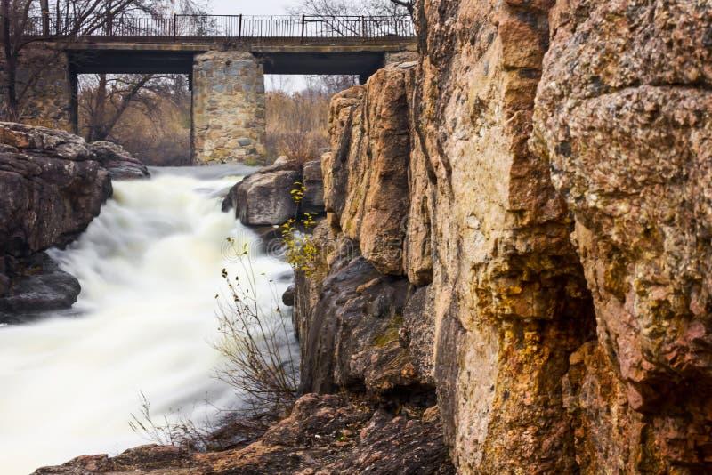 Foto atrasada do outono da ponte de pedra velha sobre o turismo e a recreação do rio da montanha fotos de stock