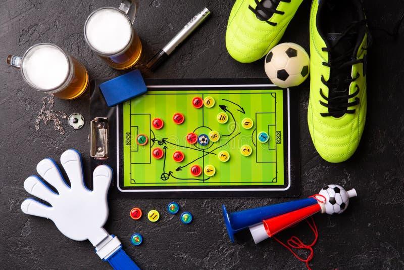 Foto auf zwei Becher Schaumbier, Tischfußball, Ball, Fußballstiefel, Rohr, Geklapperspielzeug lizenzfreie stockfotos