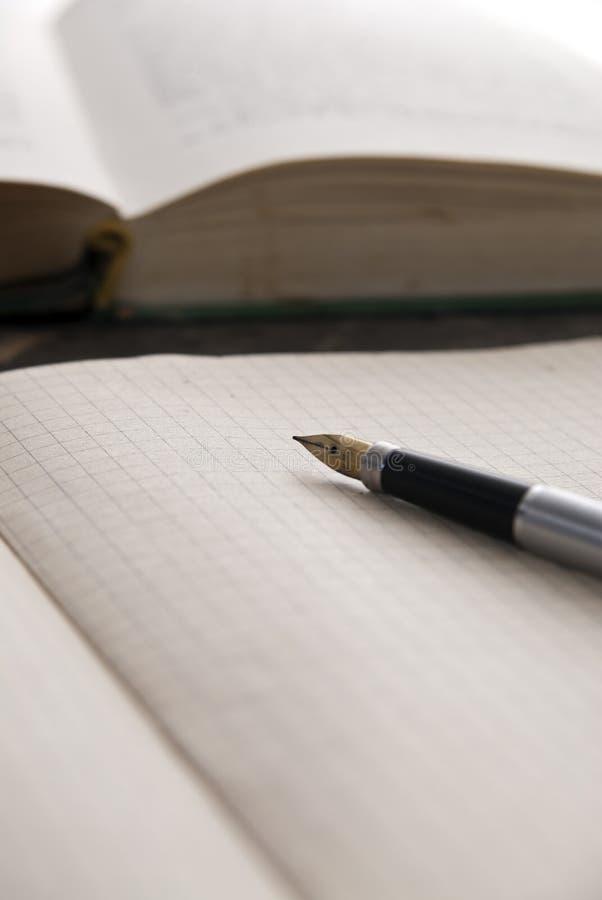 Foto av anteckningsboken och böcker på tabellen arkivfoton