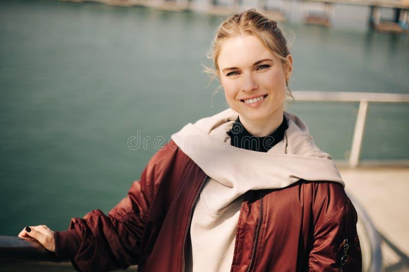 Foto av att le blondinen som ser kameran, medan stå på bron arkivfoton