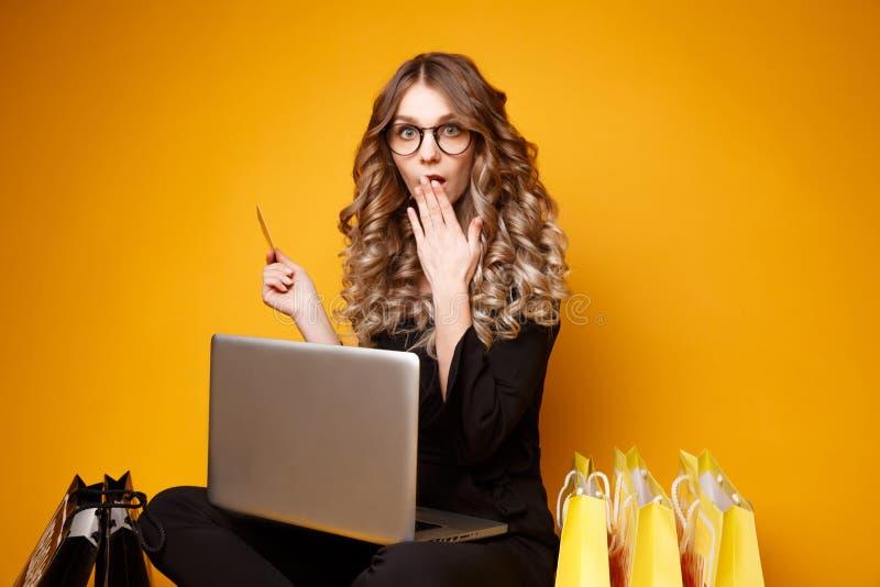 Foto av att le den stilfulla unga kvinnan som använder anteckningsboken för att shoppa direktanslutet arkivfoto