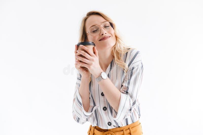 Foto av b?rande exponeringsglas f?r avkopplad trevlig kvinna som ler p? kameran och rymmer papperskoppen arkivfoton