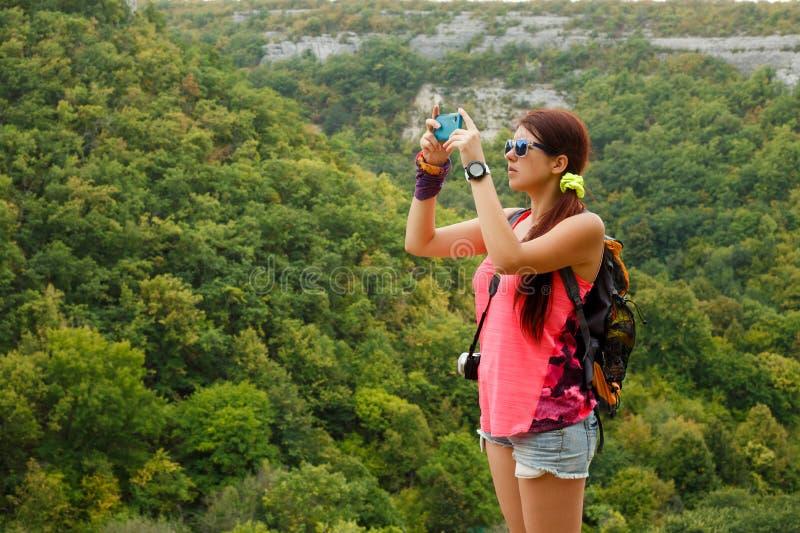 Foto av brunetten som fotograferar berget med vegetation royaltyfria bilder