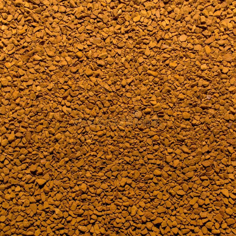 Foto av closeuptextur av brunt malt ögonblickligt kaffe, bakgrund arkivbild