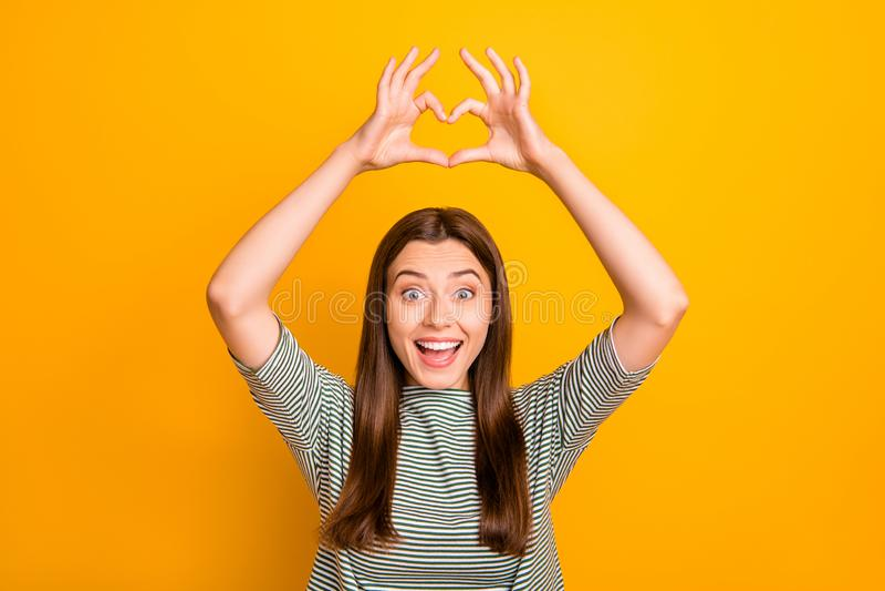 Foto av den attraktiva underbara kvinnan som kostnadsfritt gifting hennes förälskelse till dig, medan isolerat med gul bakgrund royaltyfri fotografi