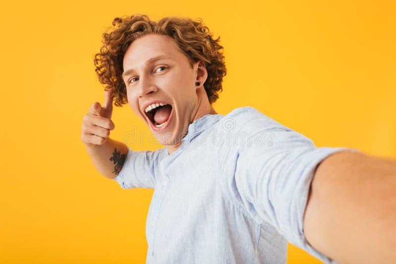 Foto av den attraktiva upphetsade man20-tal som tar selfiefotoet och poin arkivbild