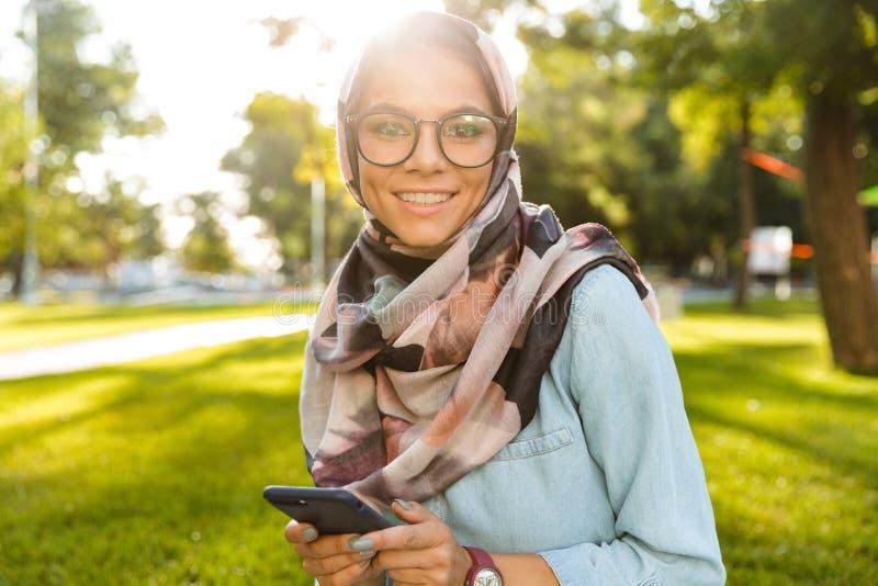 Foto av den bärande sjaletten för älskvärd arabisk kvinna genom att använda mobiltelefonen royaltyfria foton