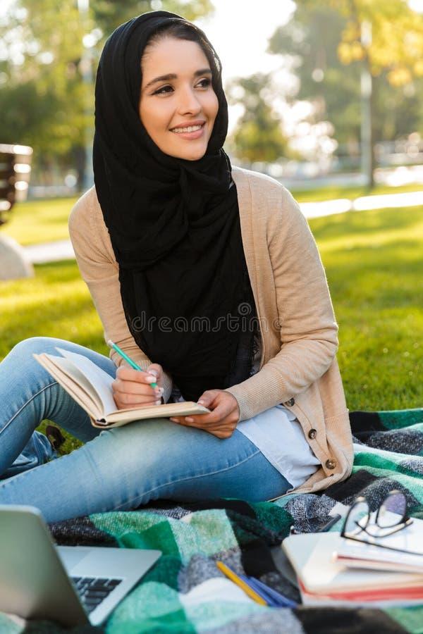 Foto av den bärande sjaletten för attraktiv arabisk kvinna som ner skriver anmärkningar i anteckningsbok royaltyfria foton