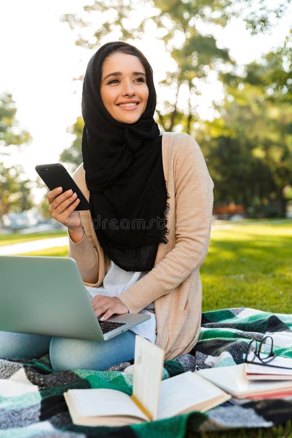 Foto av den bärande sjaletten för härlig arabisk kvinna genom att använda silverbärbara datorn arkivfoto