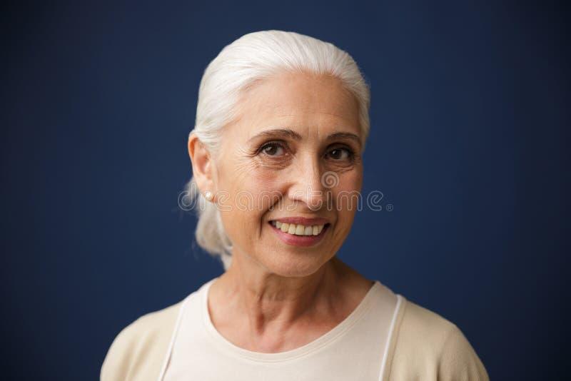 Foto av den charmiga le gamla kvinnan som ser kameran royaltyfri bild