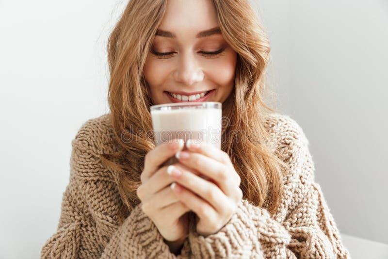 Foto av den europeiska attraktiva kvinna20-tal som dricker exponeringsglas av latte, royaltyfri foto