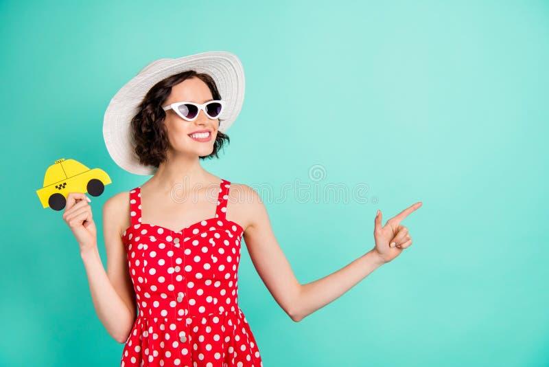 Foto av den gladlynta trevliga bärande lockheadwearen för fascinerande kvinna som pekar på taxichauffören för att göra honom att  royaltyfri foto