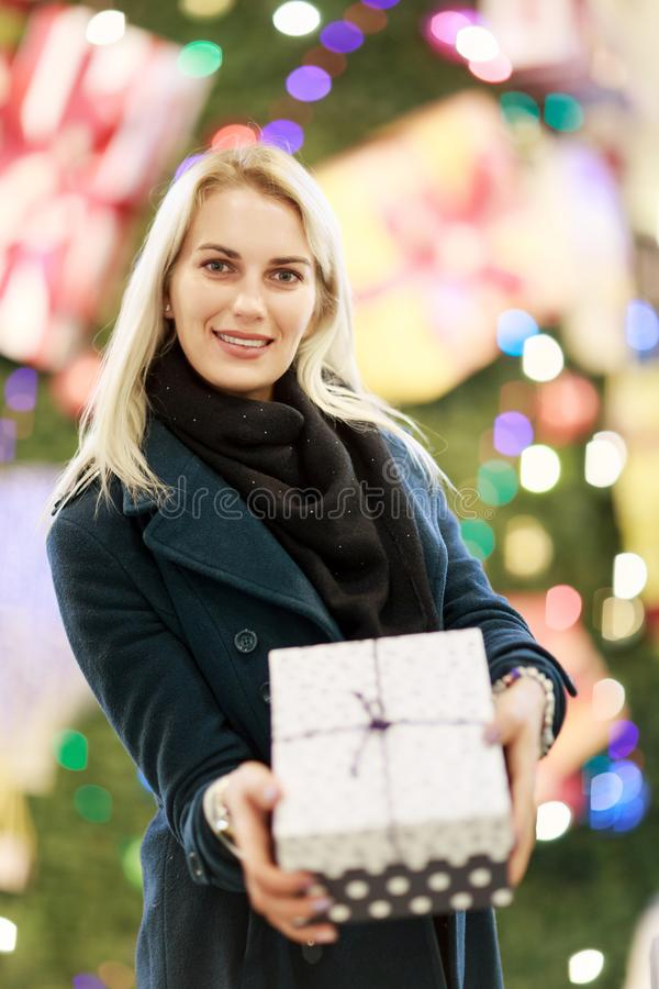 Foto av den härliga flickan i lag med gåvaasken på bakgrund av julgranen royaltyfri foto