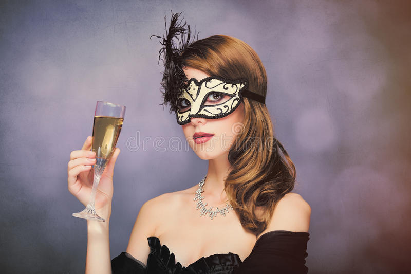 Foto av den härliga unga kvinnan i maskering med vinglaset av champag arkivbild